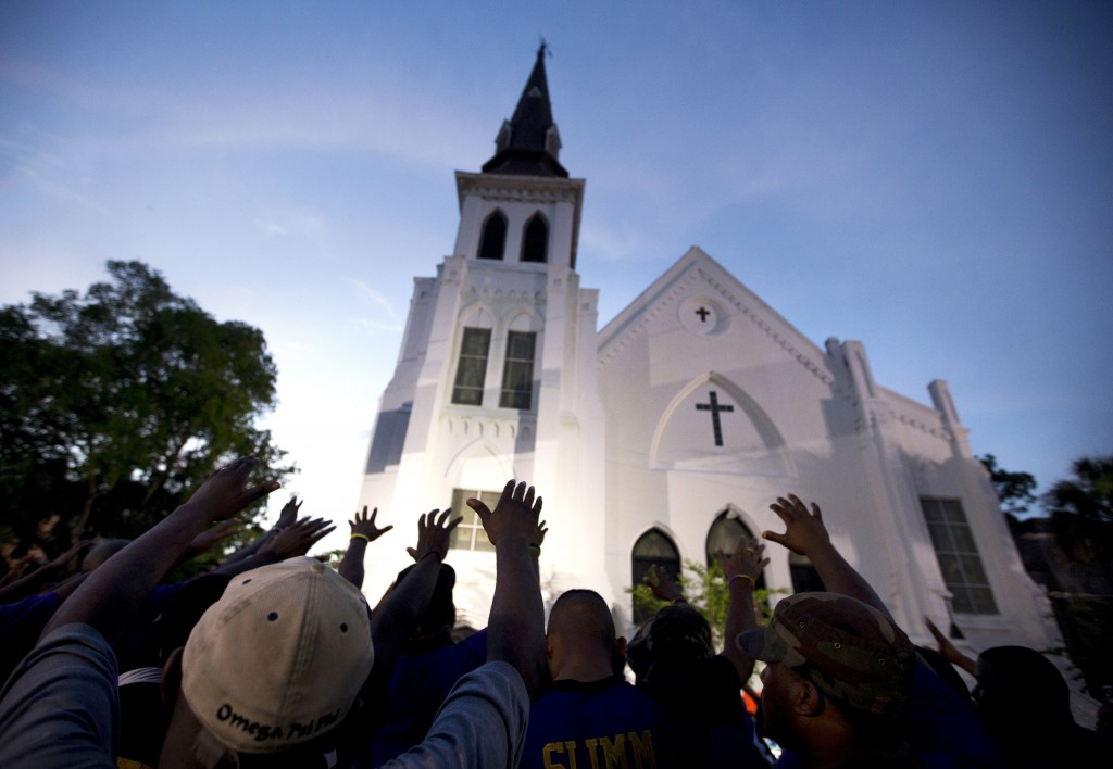FILE - In this Friday, June 19, 2015, file photo, the men of Omega Psi Phi Fraternity Inc. lead a crowd of people in prayer outside the Emanuel AME Ch...