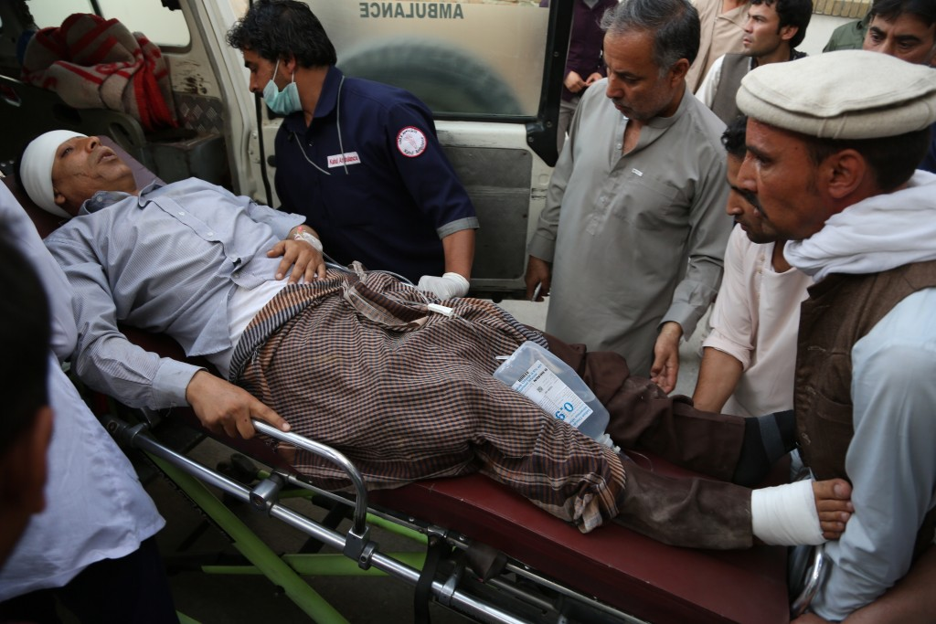 An injured man is put into an ambulance following a deadly attack outside the Rural Rehabilitation and Development Ministry in Kabul, Afghanistan, Sun...