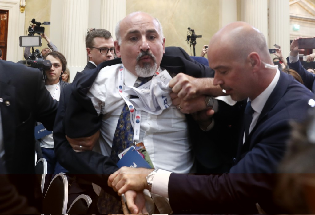 Security staff push out a man after a scuffle prior to a press conference after the meeting of U.S. President Donald Trump and Russian President Vladi...