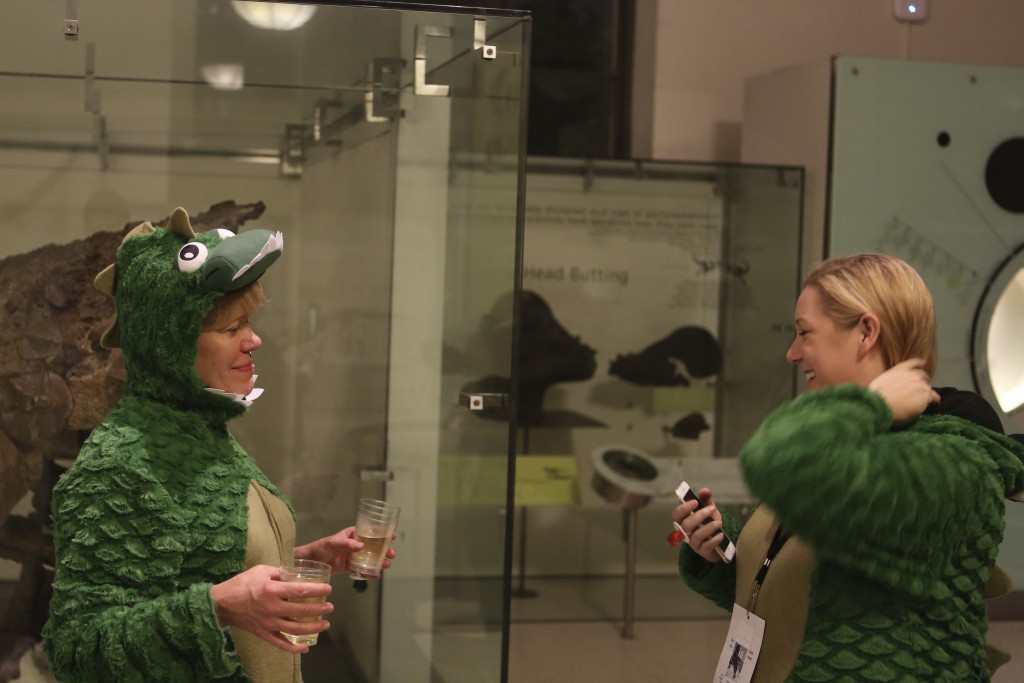 Monica Seebohm, left, and Renee Brown, right, explore the Hall of Ornithischian Dinosaurs in their Tyrannosaurus rex onesies during the adult-only sle...