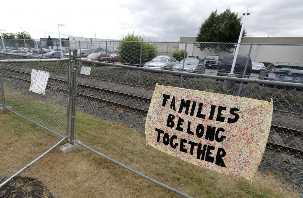 """FILE - In this July 10, 2018, file photo, a sign that reads """"Families belong Together"""" hangs on a fence outside the Northwest Detention Center in Taco..."""