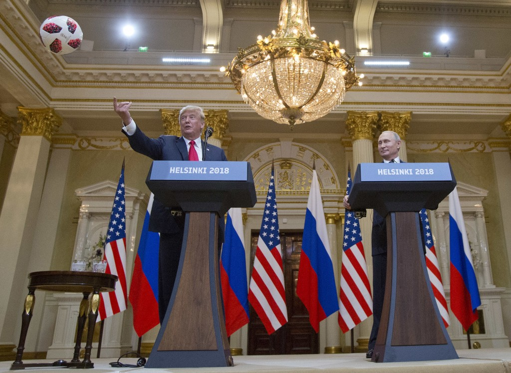 U.S. President Donald Trump, left, tosses a soccer ball to his wife first lady Melania Trump after Russian President Vladimir Putin presented it to hi...