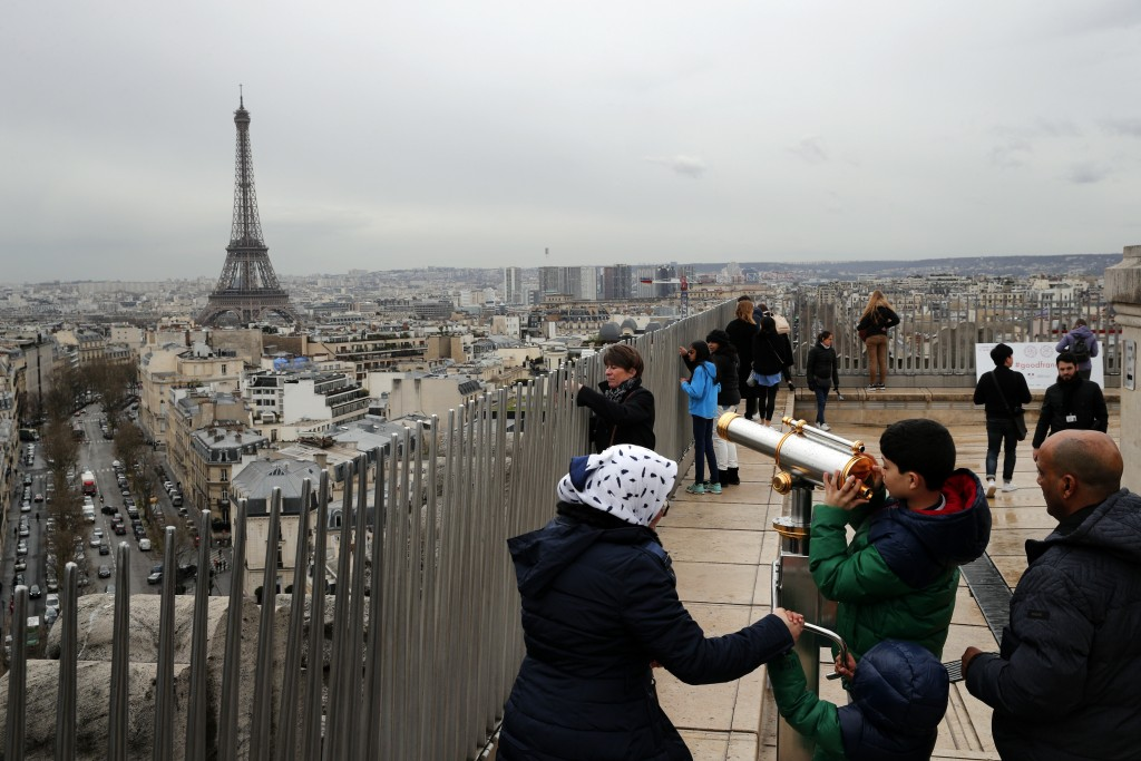 FILE - In this March 21, 2017, file photo, tourists watch Paris from the top of the Arc de Triomphe in Paris, France. The Eiffel Tower is seen backgro...