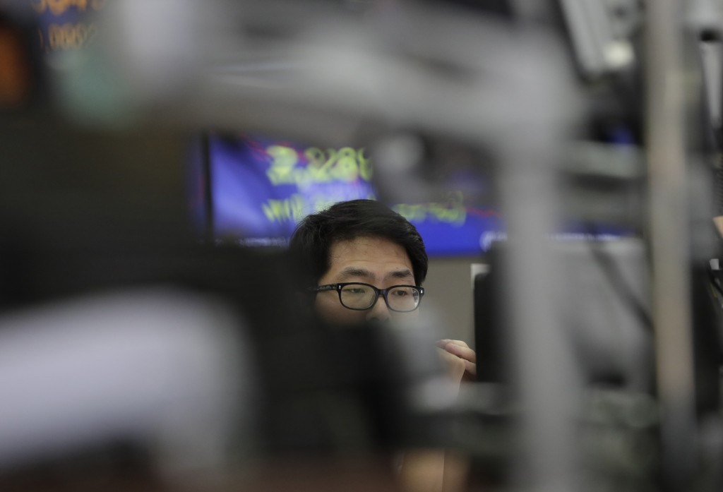 A currency trader watches monitors at the foreign exchange dealing room in Seoul, South Korea, Thursday, July 19, 2018. Asian stock markets drifted wi...