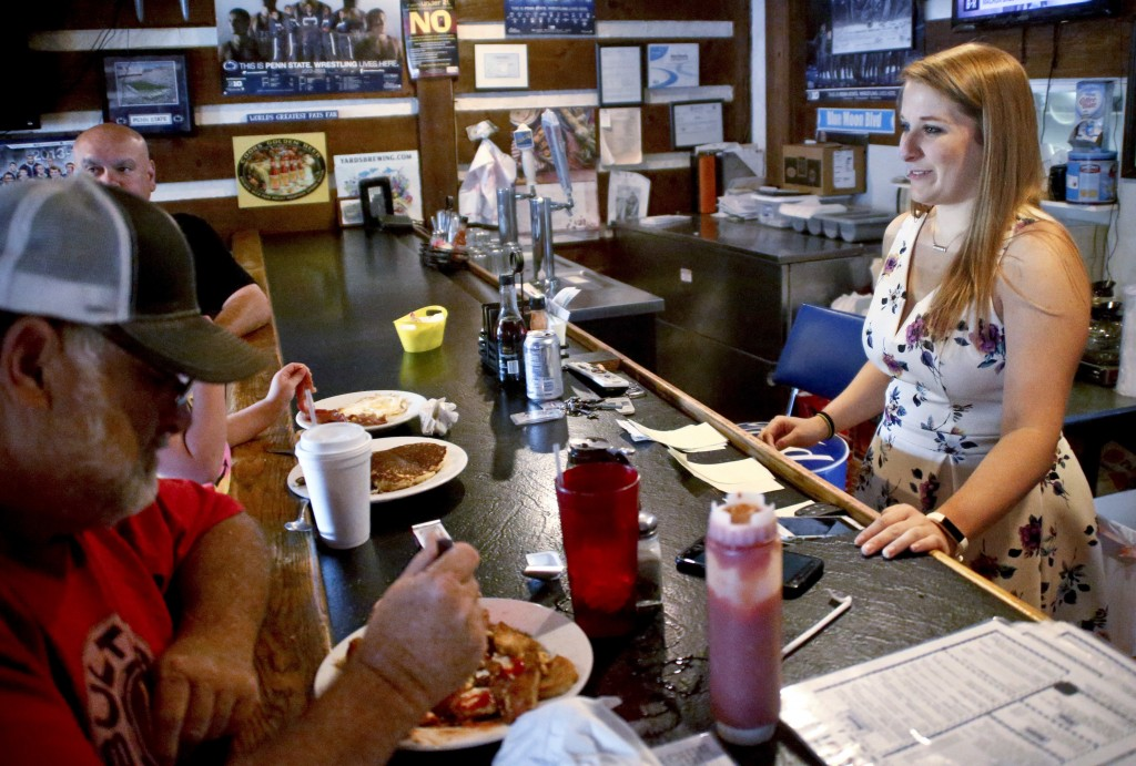 Kendra Snyder, right, talks with patrons at Checkers Bar & Grill in Mount Union, Pa., on Monday, July 16, 2018. At age 12, Snyder passed out from a co