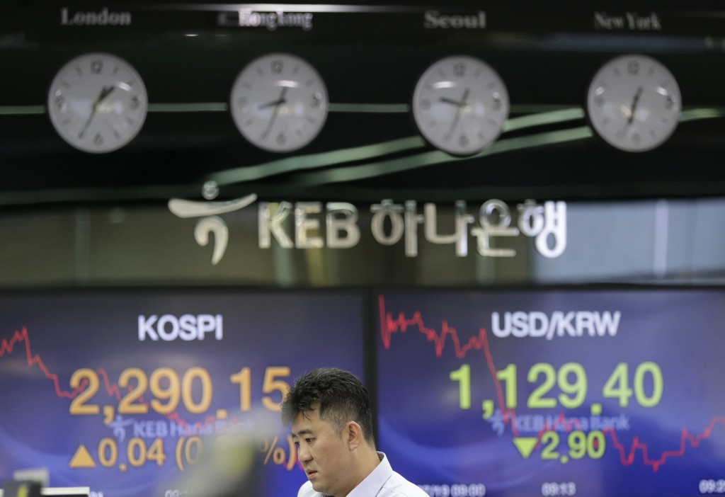 A bank employee stands near screens showing the Korea Composite Stock Price Index (KOSPI), left, and the foreign exchange rate between U.S. dollar and...