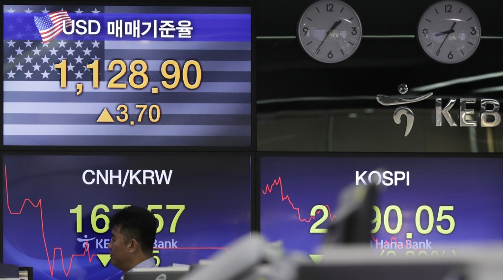 A bank employee walks by screens showing the Korea Composite Stock Price Index (KOSPI), right, and the foreign exchange rate between U.S. dollar and S...