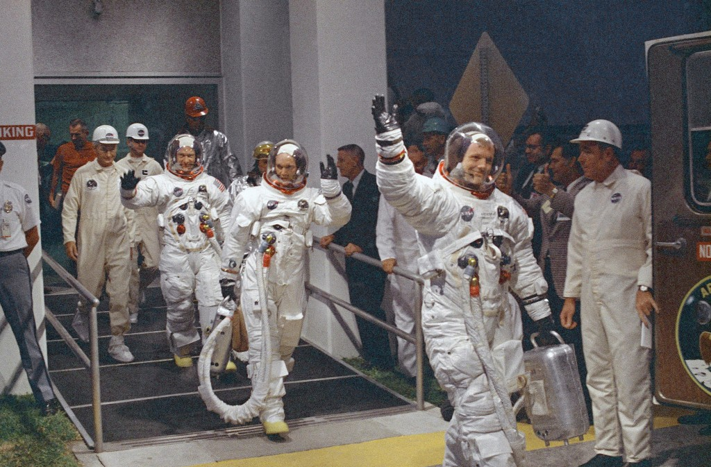 FILE - In this July 16, 1969, file photo, Neil Armstrong waving in front, heads for the van that will take the crew to the rocket for launch to the mo...