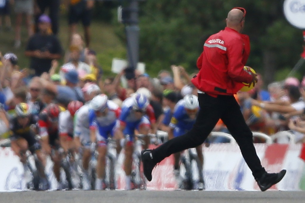 A race official runs for cover after picking up a balloon as the pack with stage winner Slovakia's Peter Sagan sprints towards the finish line of the