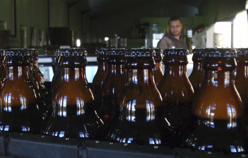 In this June 5, 2018, photo, bottles of freshly bottled beer stand in the Darling Brewery in Darling, South Africa. The South African brewery appears ...