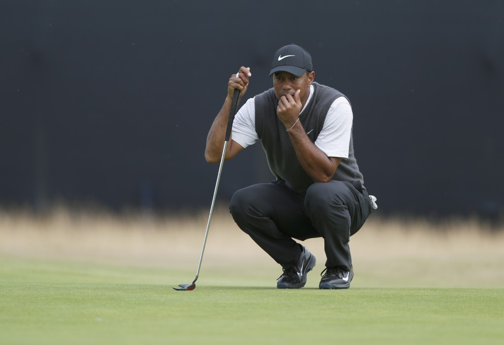 Tiger Woods of the US lines up a putt on the 13th green during the third round of the British Open Golf Championship in Carnoustie, Scotland, Saturday...