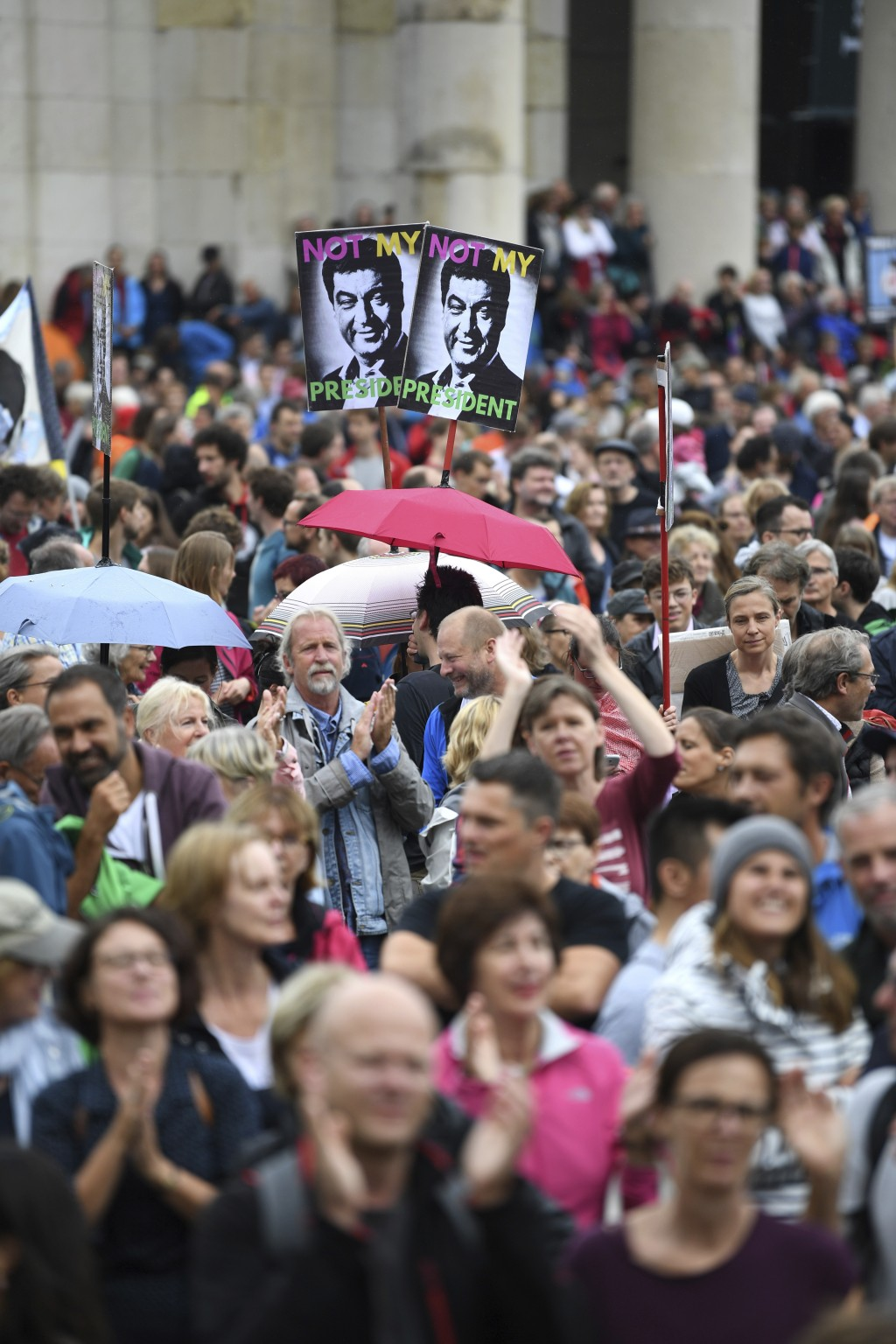 Protestors attend a demonstration under the slogan 'United Against Politics Of Fear' in Munich, Sunday, July 22, 2018. In the center a poster of Bavar...