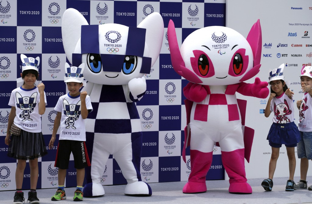 """FILE - In this July 22, 2018, file photo, Tokyo 2020 Olympic mascot """"Miraitowa"""", left, and Paralympic mascot """"Someity"""", right, pose with children for"""