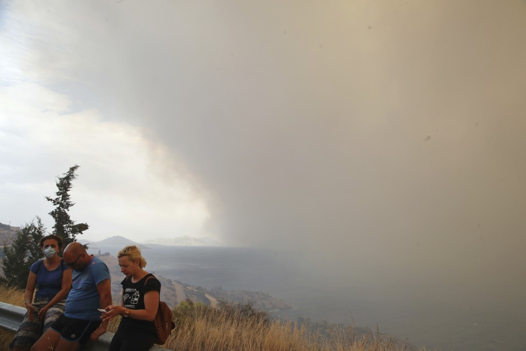 Smoke fills the sky as people sit on the roadside near Kineta, west of Athens, after roads were blocked due to forest fires Monday, July 23, 2018. Res...