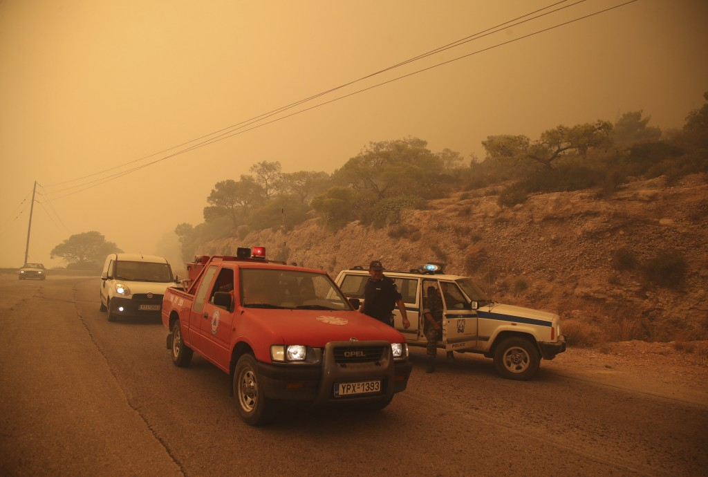 Smoke fills the sky as members of the emergency services block a road near Kineta, west of Athens, Monday, July 23, 2018. Residents were fleeing their...