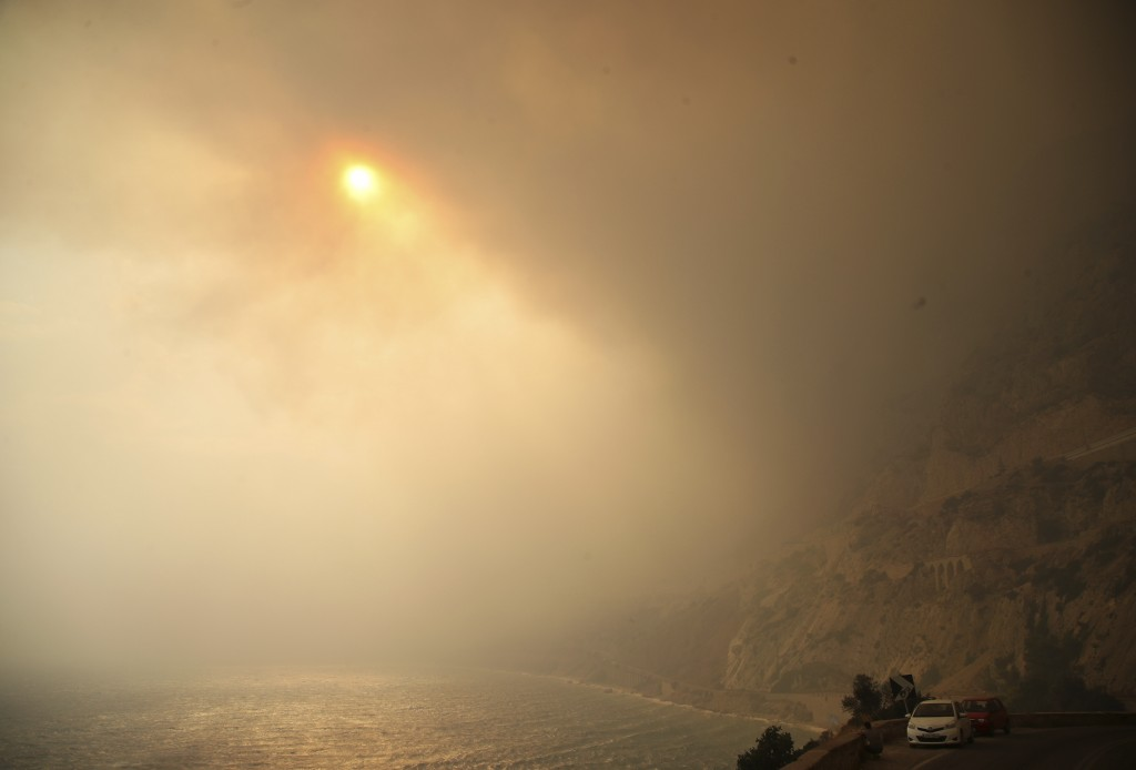 The sun breaks through a smoked filled sky as cars drive on a road near Kineta, west of Athens, Monday, July 23, 2018. Residents were fleeing their ho...
