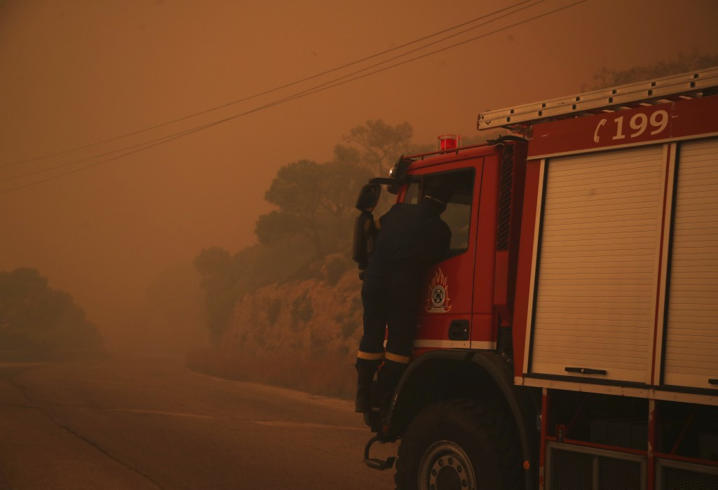 A fire truck is engulfed in a pall of orange smoke on a road near Kineta, west of Athens, Monday, July 23, 2018. Residents were fleeing their homes Mo...