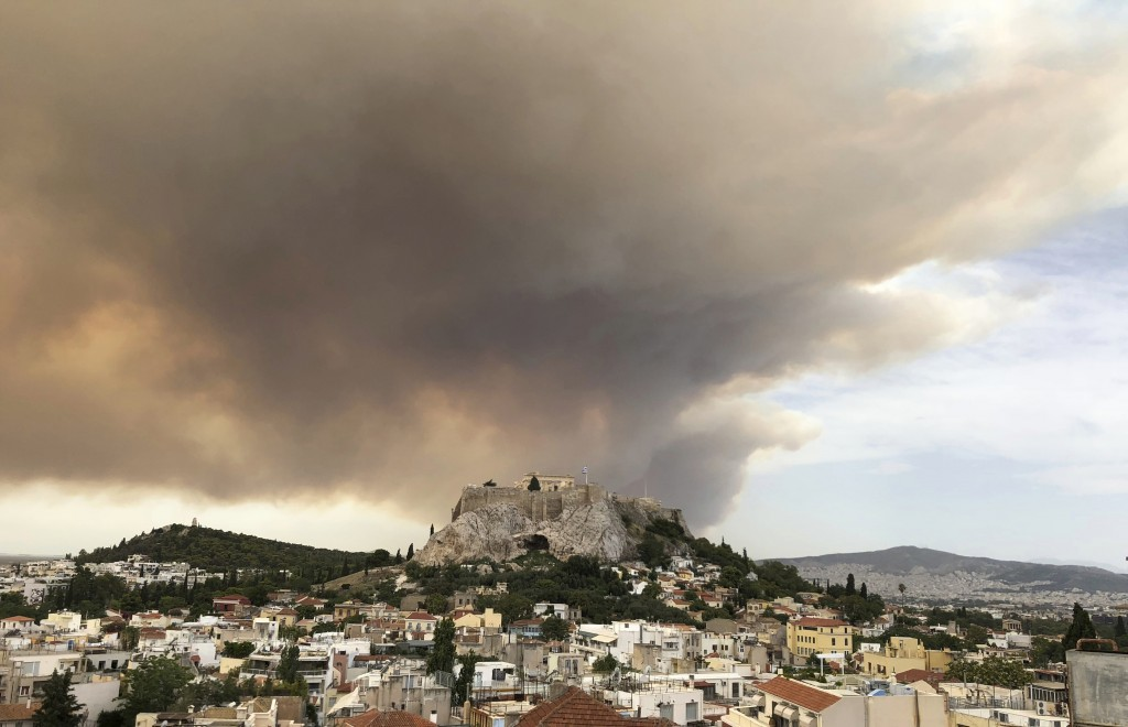 A pall of smoke turns large parts of the sky orange, with the ancient Acropolis hill at centre, as a forest fire burns in a mountainous area west of A...