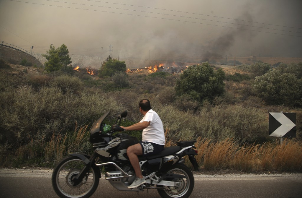 A motorcyclist looks at smoldering shrubbery on a road near Kineta, west of Athens, Monday, July 23, 2018. Residents were fleeing their homes Monday a...