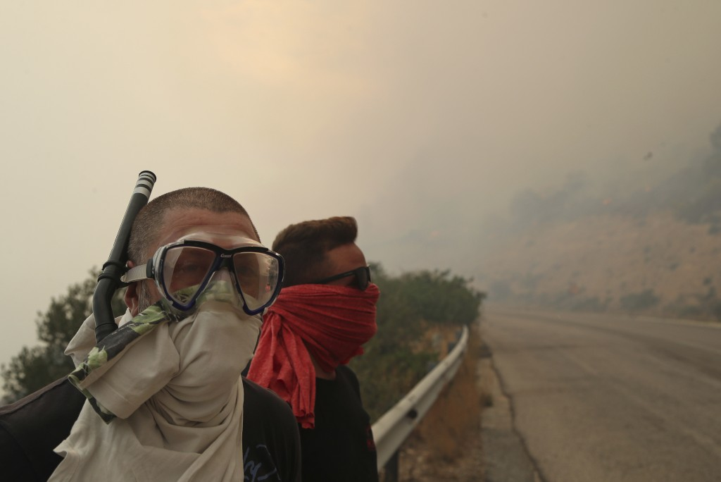 People cover their faces from the smoke that fills the sky near Kineta, west of Athens, after roads were blocked due to forest fires Monday, July 23, ...