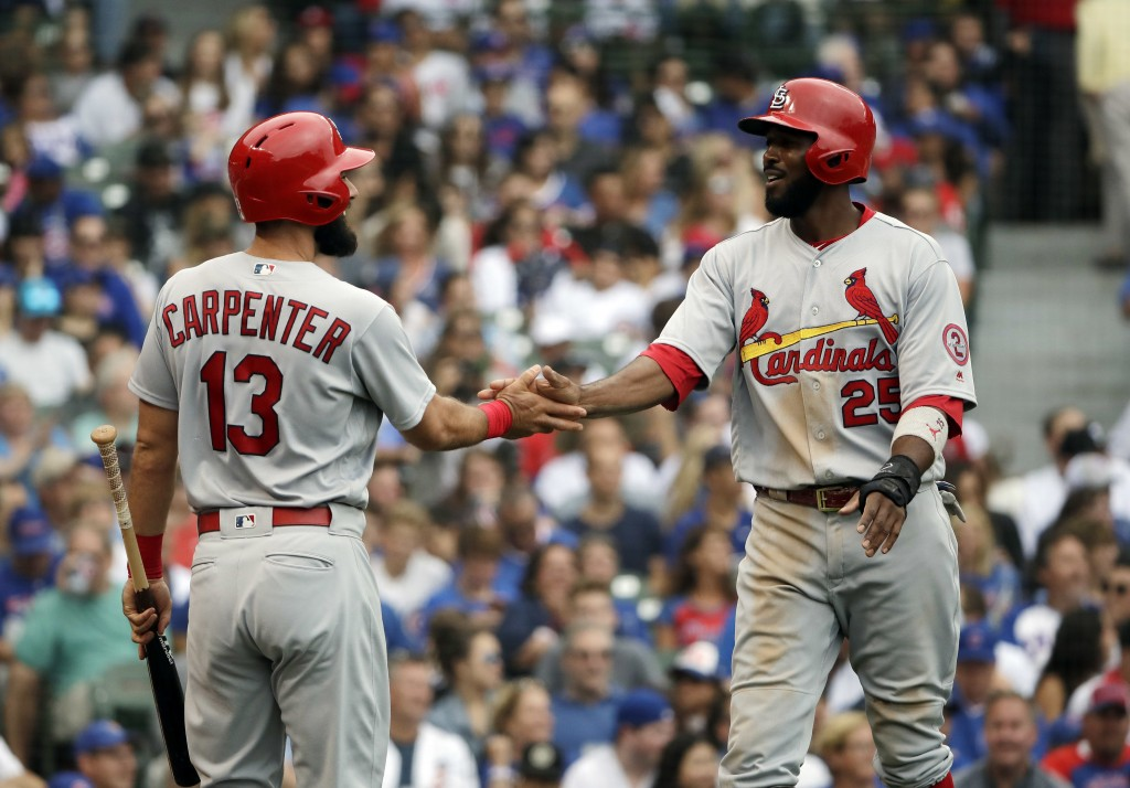 St. Louis Cardinals' Dexter Fowler, right, celebrates with Matt Carpenter after scoring on a one-run double by Yairo Munoz during the fourth inning of...
