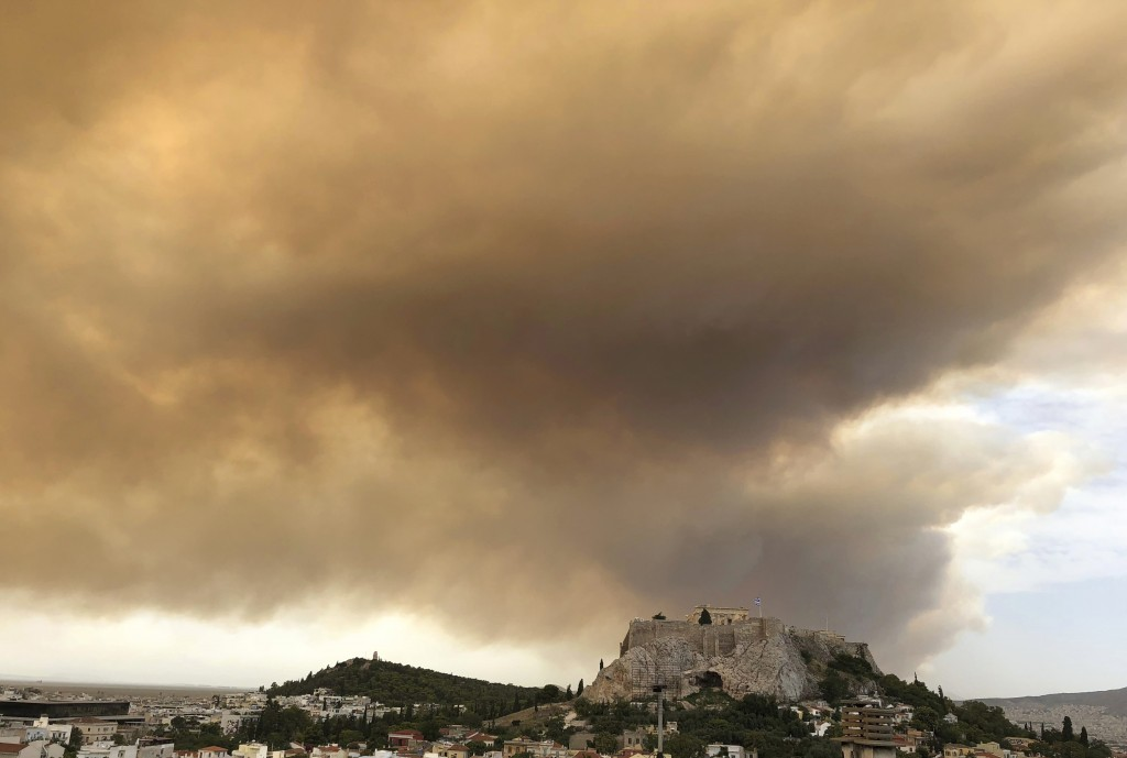 A plume of smoke turns large parts of the sky orange, with the ancient Acropolis hill at centre, as a forest fire burns in a mountainous area west of ...