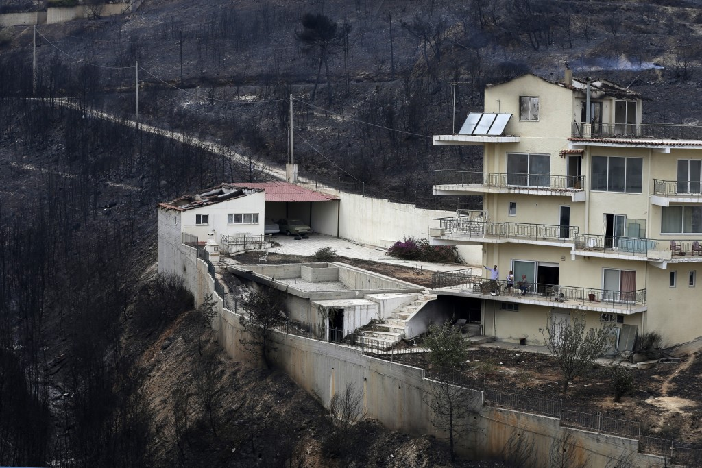 People look the burned forest from their balcony in Neos Voutzas, east of Athens, Tuesday, July 24, 2018. Wildfires raged through seaside resorts near...