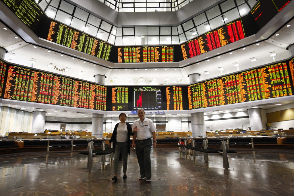 Investors walk in front of trading boards at a private stock market gallery in Kuala Lumpur, Tuesday, July 24, 2018. Asian markets rose on Tuesday as ...