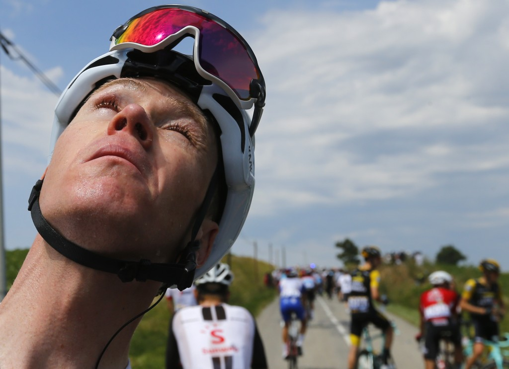 Britain's Chris Froome grimaces after he treated his eyes for tear gas or pepper spray sprayed on the peloton when a farmer's protest interrupted duri...