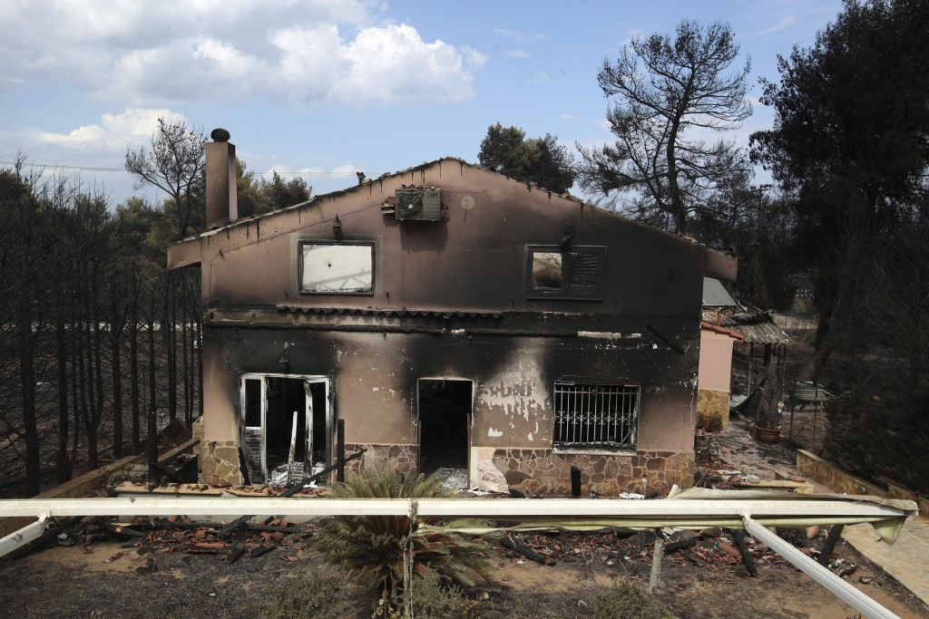A burned house is seen in Agios Andreas, east of Athens, Tuesday, July 24, 2018. Wildfires raged through seaside resorts near the Greek capital, torch...