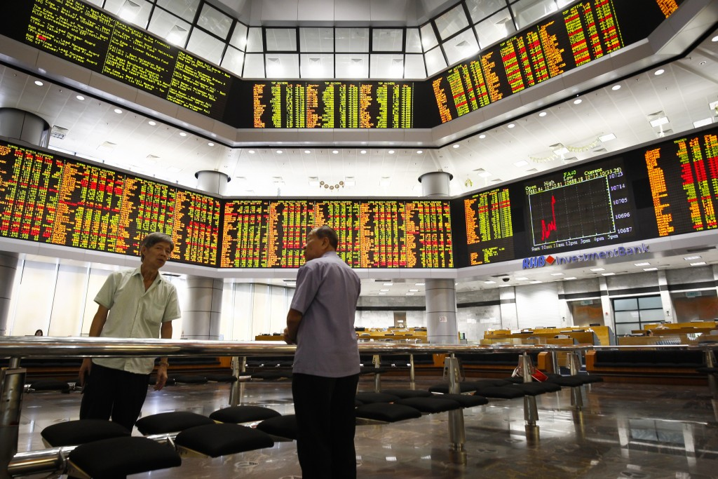 Investors stand in front of trading boards at a private stock market gallery in Kuala Lumpur, Tuesday, July 24, 2018. Asian markets rose on Tuesday as...