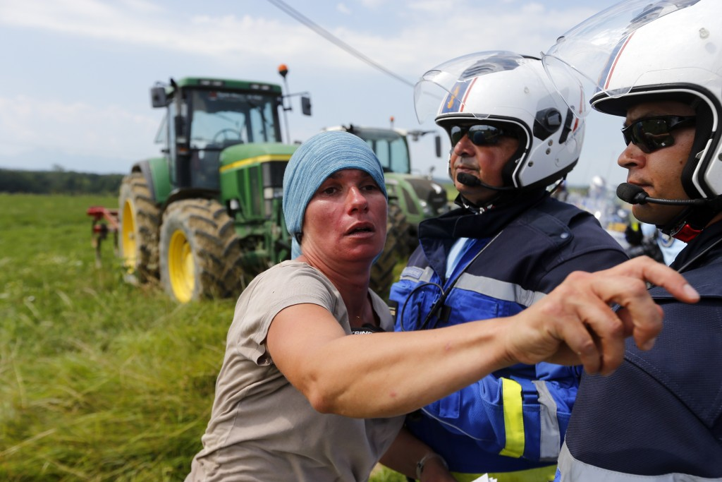 A protestor faces French gendarmes during the sixteenth stage of the Tour de France cycling race over 218 kilometers (135.5 miles) with start in Carca...
