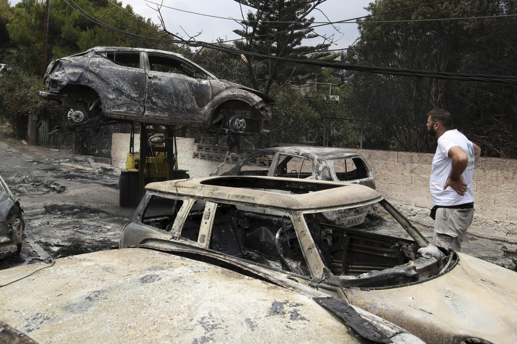 A crane removes a burned car from the road in Mati, east of Athens, Tuesday, July 24, 2018. Wildfires raged through seaside resorts near the Greek cap...