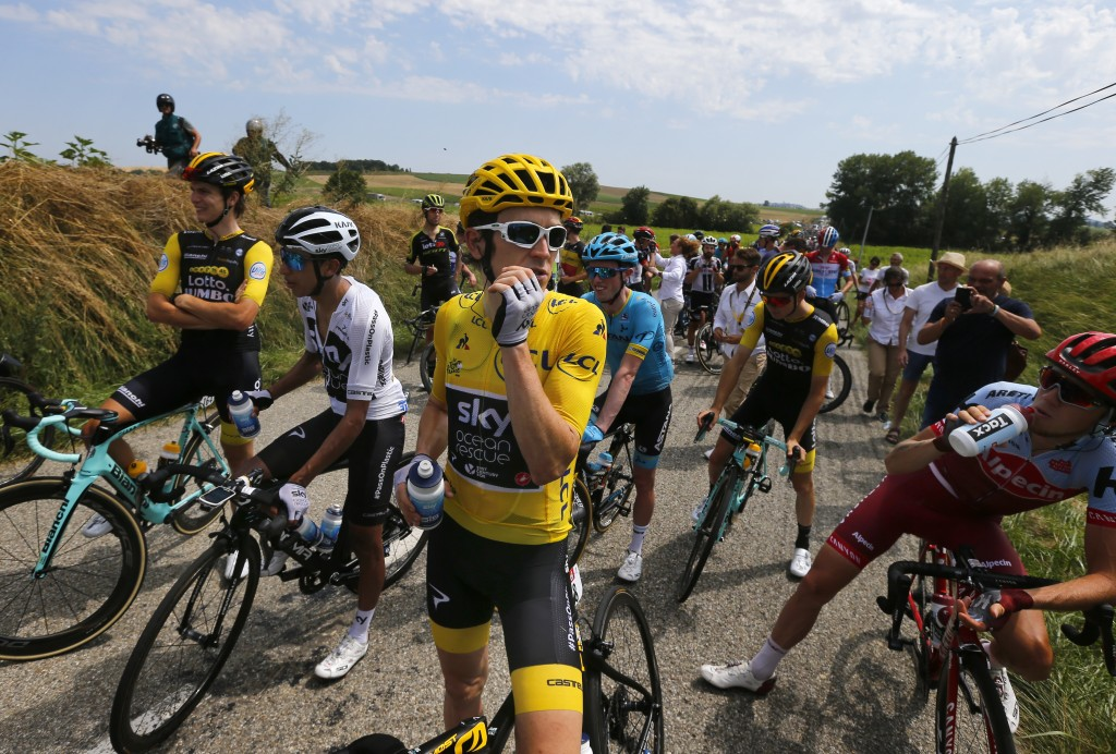 Riders with Britain's Geraint Thomas, wearing the overall leader's yellow jersey Britain's wait on the road after a farmer's protest interrupted the s...