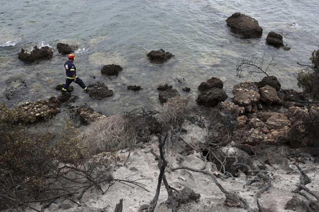 A member of a rescue team searches the area where burned trees hug the coastline in Mati, east of Athens, Tuesday, July 24, 2018. Wildfires raged thro...