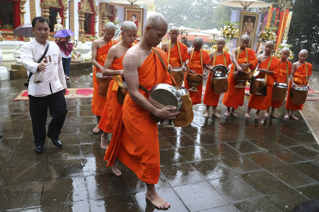 Soccer coach Ekkapol Chanthawong, front, and members of the soccer team who were rescued from a flooded cave, attend a Buddhist ceremony as they prepa...