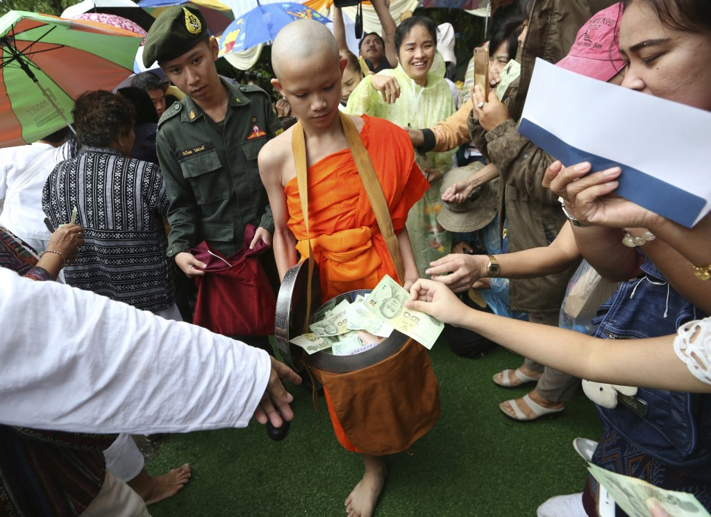 Followers offer banknotes to soccer team member Mongkol Boonpiam, as he and his other teammates and coach are ordained as Buddhist monks and novices f...