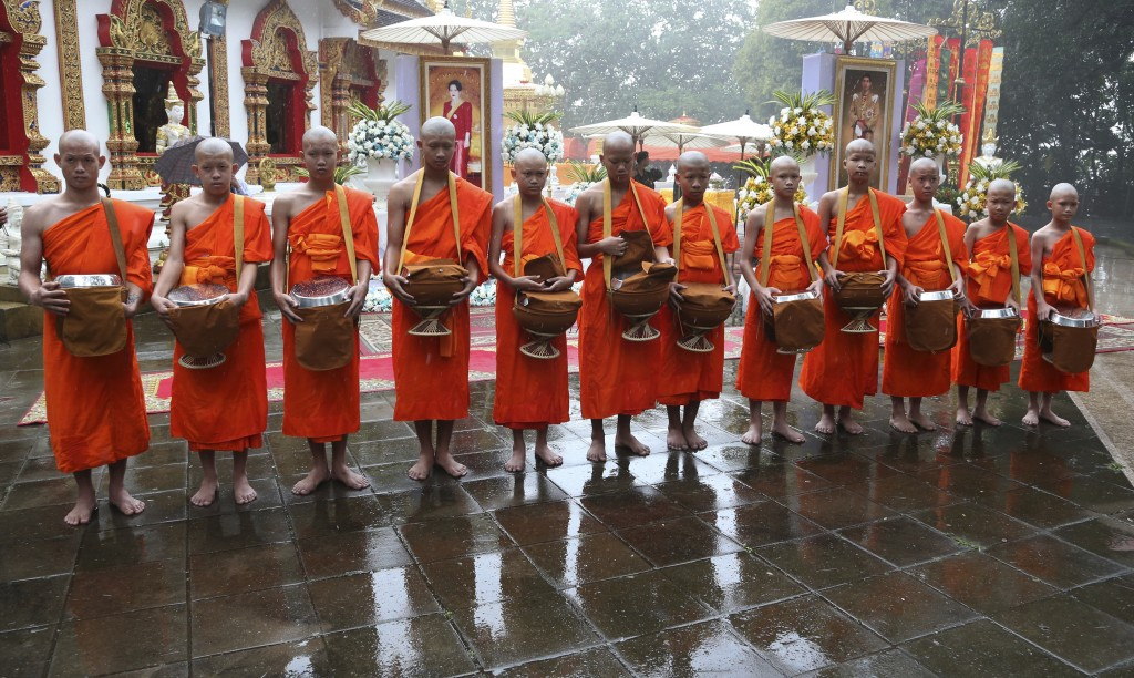 Soccer coach Ekkapol Chanthawong, left, and members of the soccer team who were rescued from a flooded cave, attend a Buddhist ceremony as they to be ...