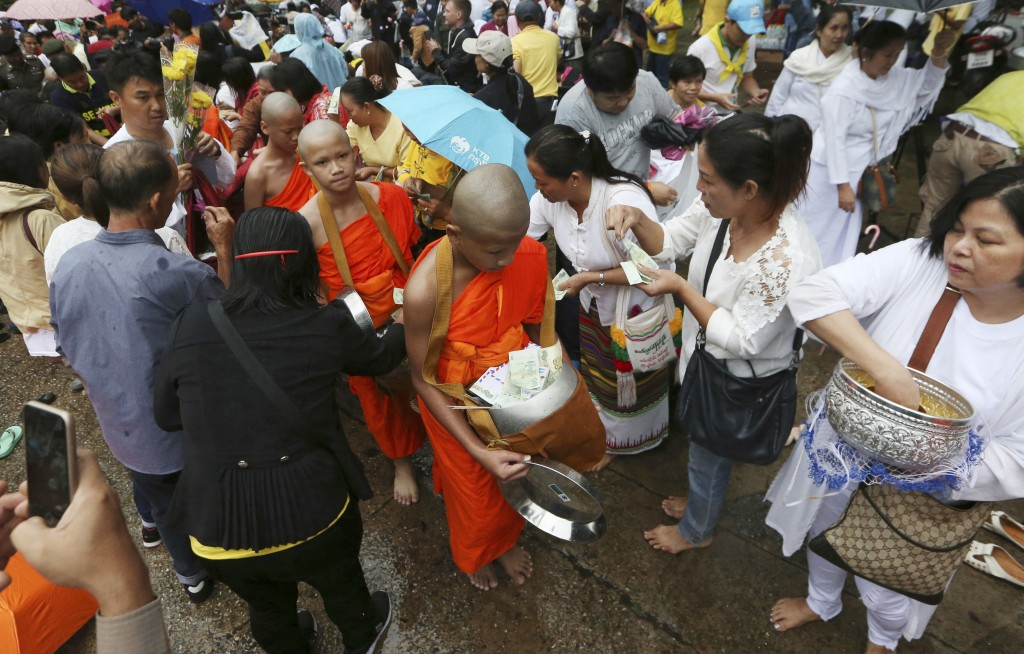 Followers offer banknotes to soccer team members as they are ordained as Buddhist monks and novices following their dramatic cave rescue last week in ...