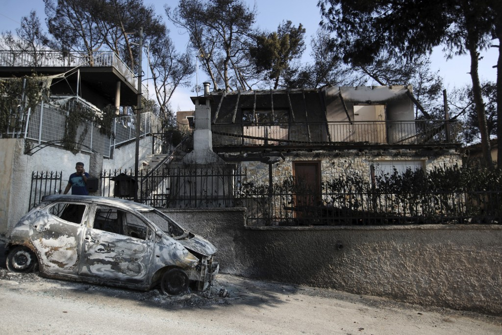 A man stands next to his burned house and car as he speaks on his cellphone in Mati, east of Athens, Wednesday, July 25, 2018. Rescue crews were searc...