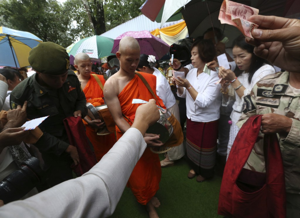 Followers offer banknotes to the soccer team member as they are ordained as Buddhist monks and novices following their dramatic cave rescue last week ...