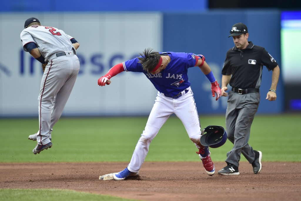 Toronto Blue Jays' Lourdes Gurriel Jr., right, is safe at second base with a double as Minnesota Twins second baseman Brian Dozier (2) is pulled off t...