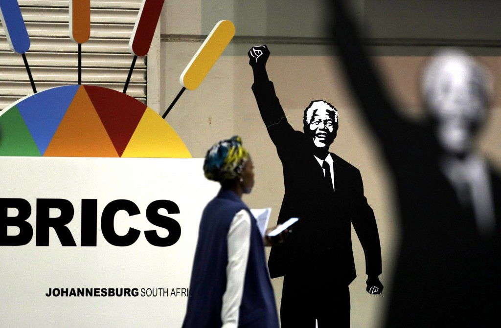 A journalist walks past a placard of Nelson Mandela during the BRICS Summit in Johannesburg, South Africa. (AP Photo/Themba Hadebe)