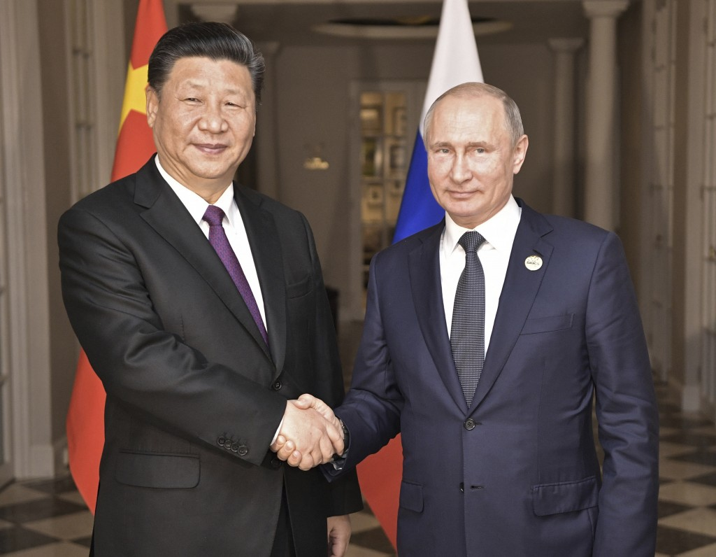 China's President Xi Jinping, left, poses with Russia's President Vladimir Putin for a photo at the BRICS summit in Johannesburg, South Africa, Thursd