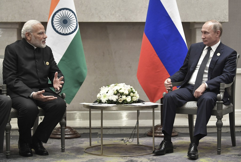 Indian Prime Minister Narendra Modi, left, speaks to Russia's President Vladimir Putin at the BRICS summit in Johannesburg, South Africa, Thursday, Ju