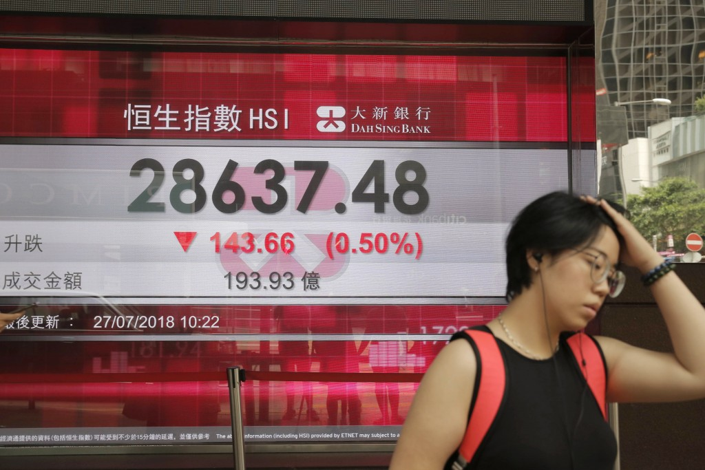 A woman walks past an electronic board showing Hong Kong share index outside a bank in Hong Kong Friday