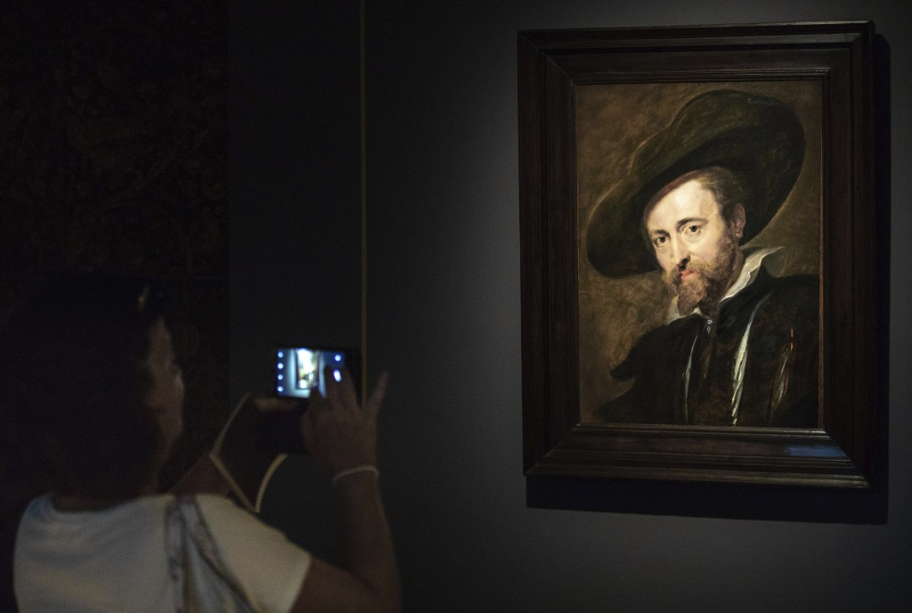 In this photo taken on Thursday, July 26, 2018, a visitor looks at the restored Peter Paul Rubens self portrait from 1628 in the Rubenshouse in Antwer...