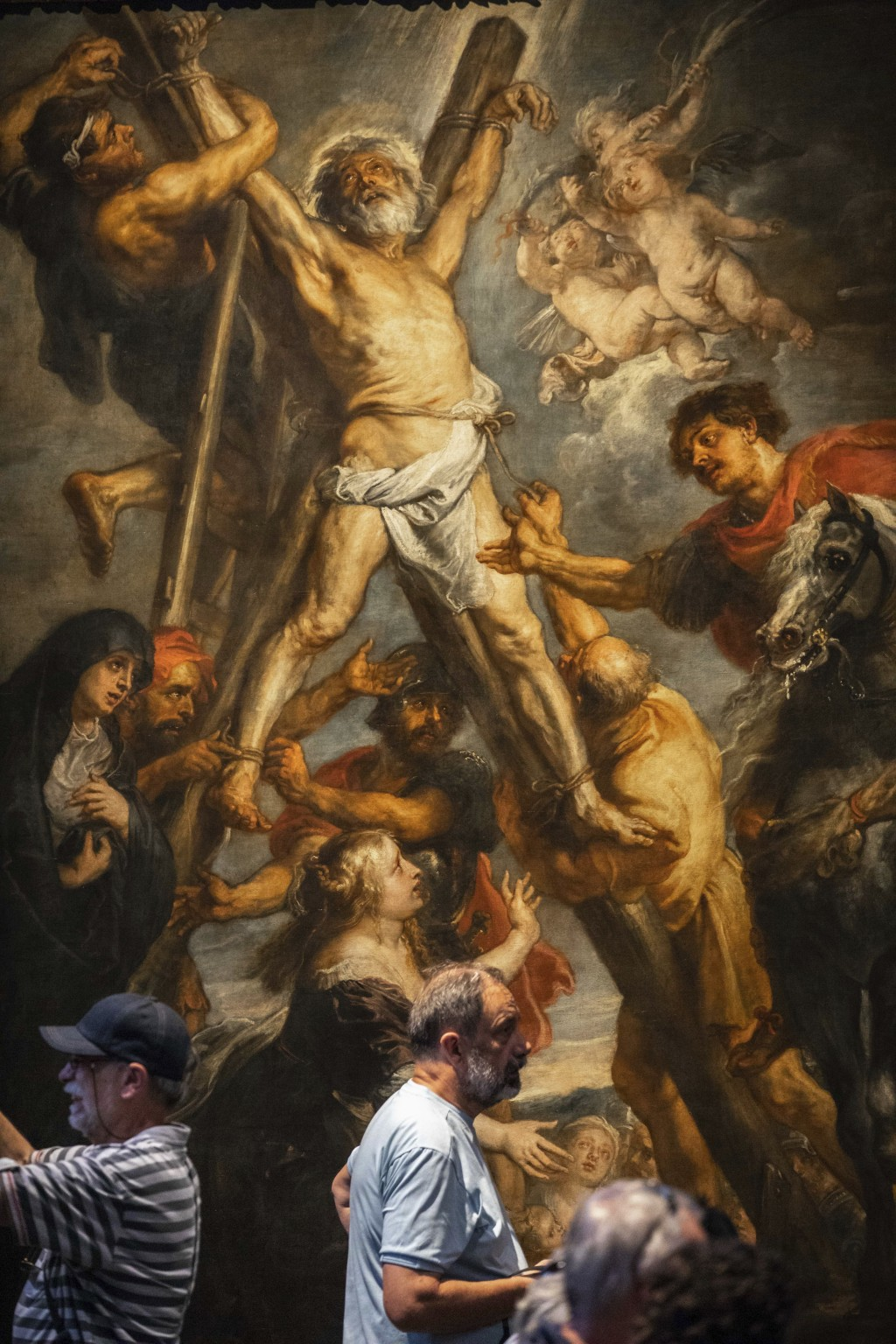 """In this photo taken on Thursday, July 26, 2018, visitors look at the painting """"The Martyrdom of St. Andrew"""" by Flemish master Peter Paul Rubens in the..."""