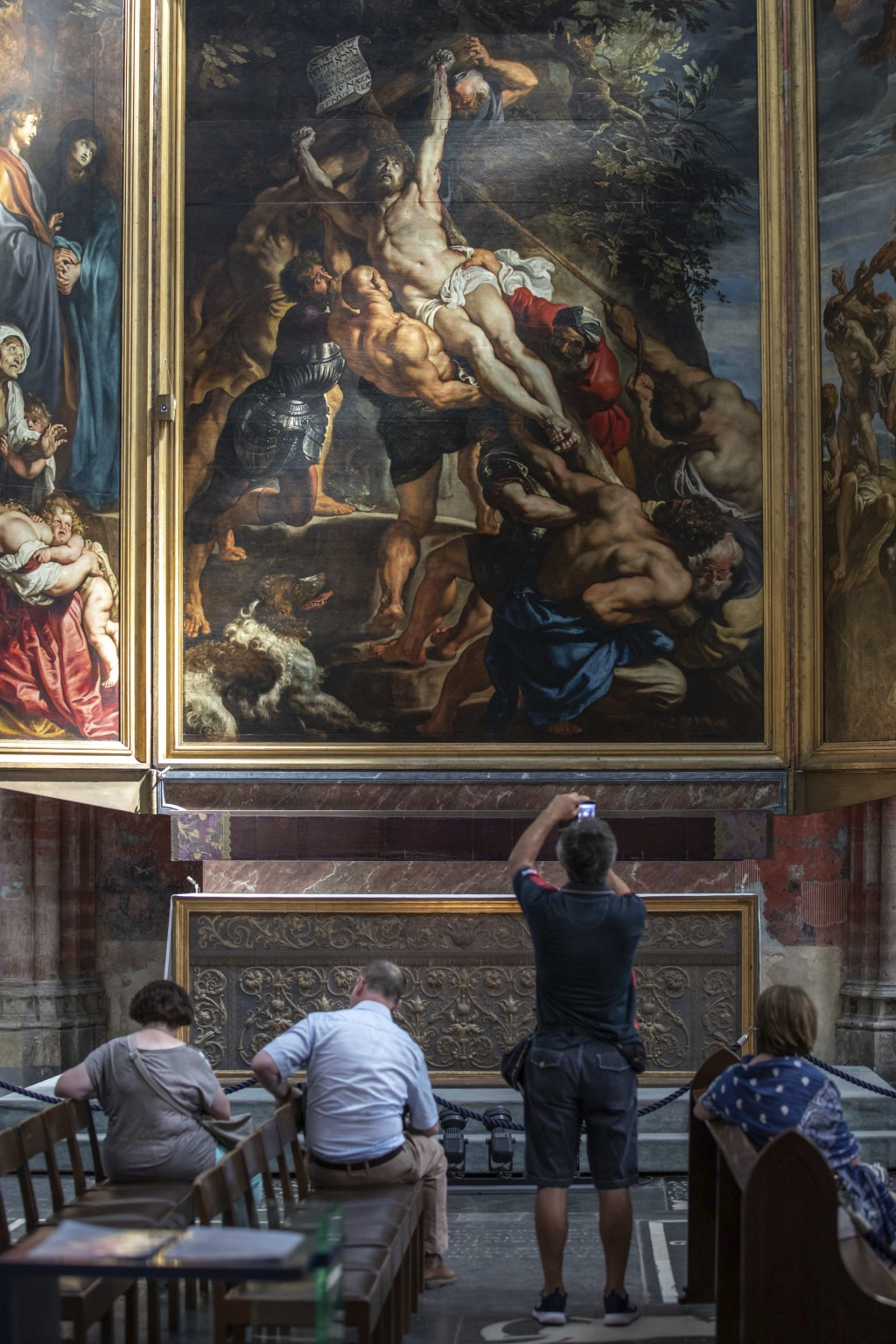 "In this photo taken on Thursday, July 26, 2018, visitors look at the painting ""The Raising of the Cross"" by Flemish master Peter Paul Rubens in the Ou"