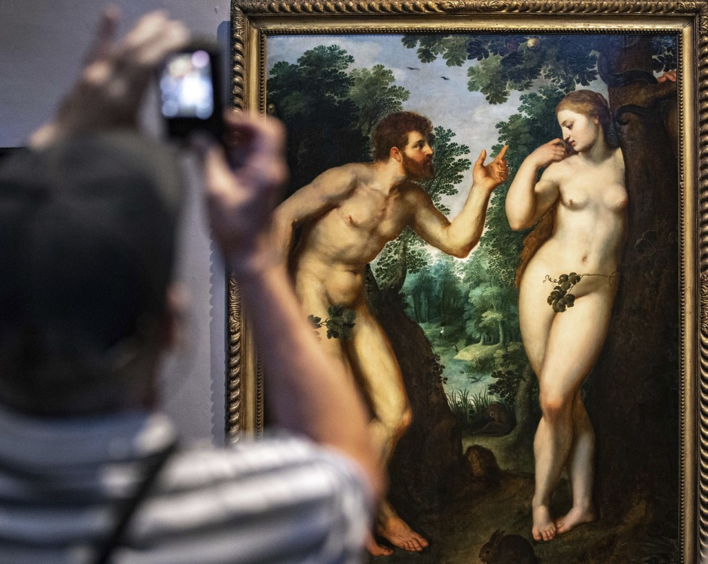 """In this photo taken on Thursday, July 26, 2018, visitors look at the painting """"Adam and Eve"""" by Flemish master Peter Paul Rubens in the Rubenshouse in..."""